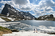 Two female hikers are crossing a snow field at the lake Geisspfadsee with the peaks of the Rothorn and the Schwarzhorn, Landschaftspark Binntal, Valais, Switzerland