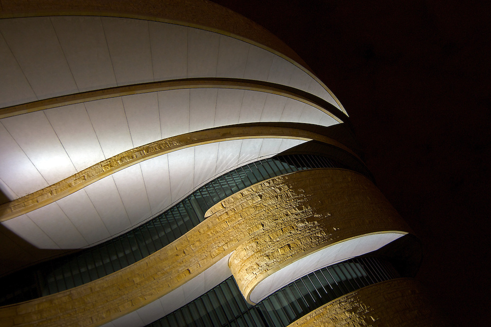Night, exterior image of the Smithsonian Institution's National Museum of the American Indian (NMAI), the first national museum dedicated to the preservation, study, and exhibition of the life, languages, literature, history, and arts of Native Americans.