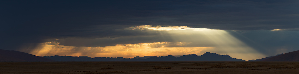 Sunlight shines through dark storm clouds, lighting the desert below, Namib-Naukluft National Park, Namibia.