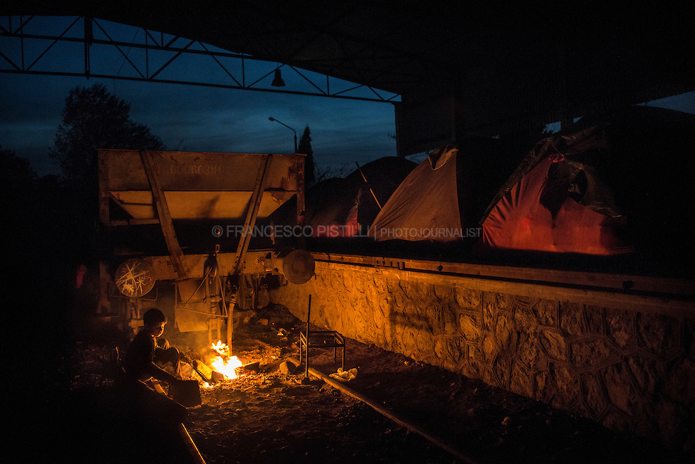A refugee kid sits around a fire in a railway repairs hangar where thousand of refugees have set up their tents at the northern Greek border point of Idomeni, Greece (Europe).
