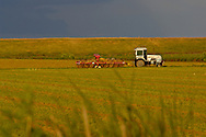 Farm tractor in field below dark storm clouds at sunset, near Rio Vista, Solano County, California