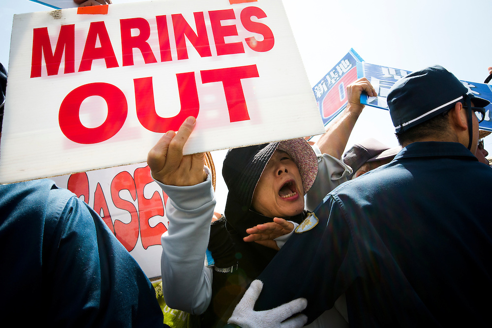 OKINAWA, JAPAN - JUNE 17 : A female protester holding a banner 'Marines Out' demanding the withdrawal of US bases from Okinawa, takes part in a rally in front of the US base in Camp Schwab, on June 17, 2016 in Nago, Okinawa, Japan. Protests have grown more intense in the past days due to the past incident of rape of a Japanese woman and drunk driving in Okinawa over American military presence in Japan. Photo: Richard A. de Guzman