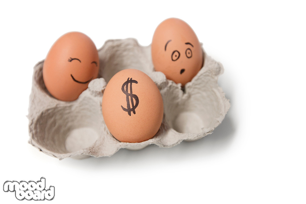 Three eggs in carton with a dollar sign on one egg
