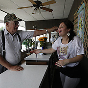 Jamie Hackney laughs with Bob Ethington, a regular customer, who teases her whenever he comes in the shop. ?Sometimes people will stay and chat for hours,? says Jamie, ?They all know my dad, but when he's not here, they talk with me. Sometimes I have to hide if I need to get work done.? .