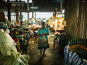 14 DECEMBER 2015 - BANGKOK, THAILAND: A woman walks through Bang Chak Market. The market closes permanently on Dec 31, 2015. The Bang Chak Market serves the community around Sois 91-97 on Sukhumvit Road in the Bangkok suburbs. About half of the market has been torn down. Bangkok city authorities put up notices in late November that the market would be closed by January 1, 2016 and redevelopment would start shortly after that. Market vendors said condominiums are being built on the land.       PHOTO BY JACK KURTZ