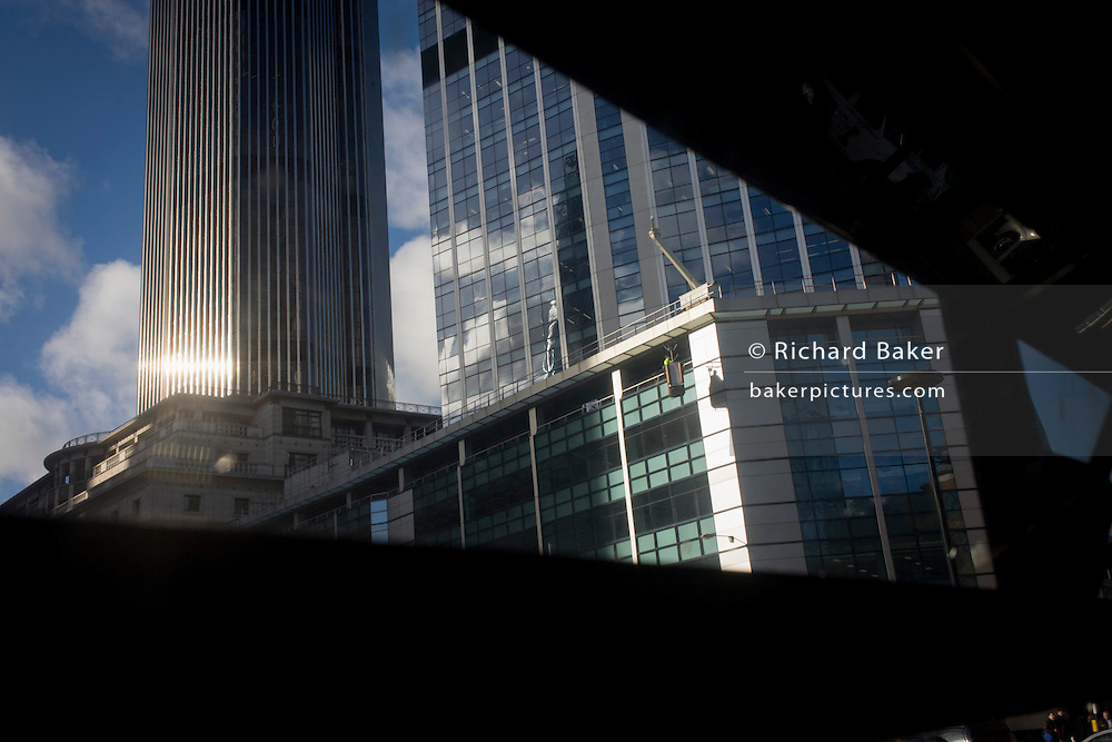 Seen through a bus window, window cleaners hang on the side of a city office block in the financial City of London.