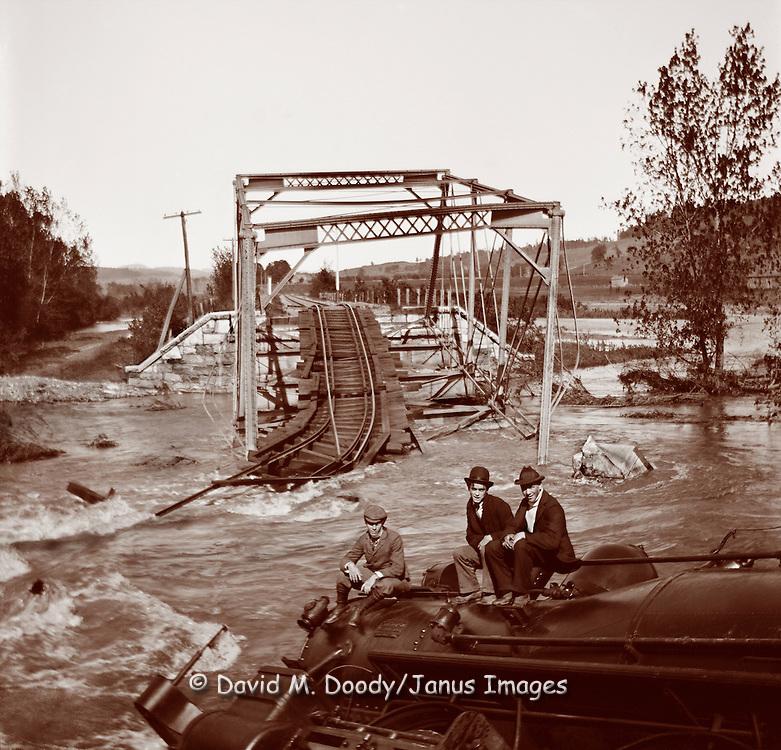 3 curious men sit atop a derailed locomotive next to a flood swollen river. Train wreck at a broken bridge, probably the result of a flood circa 1900.