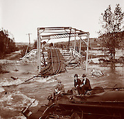 3 curious men sit atop a derailed locomotive next to a flood swollen river. Train wreck at a broken bridge, probably the result of a flood circa 1900.
