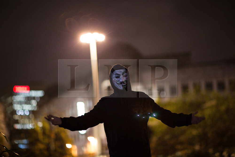© Licensed to London News Pictures . 05/11/2015 . Manchester , UK . A protester wearing a Guy Fawkes masks at an Anonymous demonstration in Manchester , UK , this evening (5th November 2015) . Photo credit : Joel Goodman/LNP