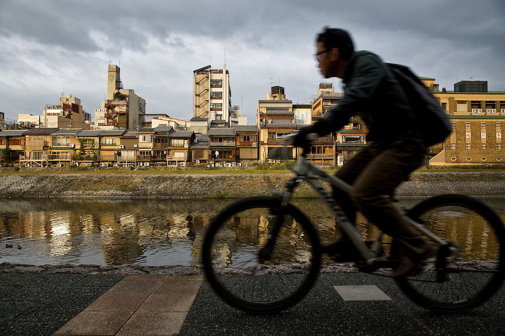 Kamo River, Kyoto, Japan.  A man rides his bicycle during the morning commute along the banks of the Kamo river, with traditional Japanese houses on the other side.