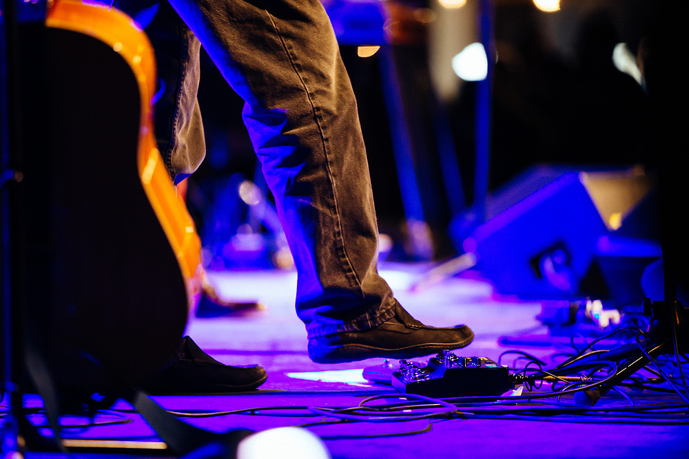 Robert Earl Keen performs to a packed crowd in Jackson, Wyoming. Guitarist Bill Whitbeck hits one of his pedals.