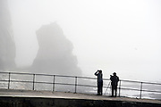 © Licensed to London News Pictures. 14/04/2015. Seaford, UK. Birdwatchers scan the mist for sea birds. . People in the early morning sea mist and sunshine in Seaford today 14th April 2015. Today is expected to be a very warm day across Britain. . . Photo credit : Stephen Simpson/LNP