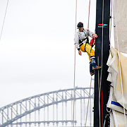 Crew members fixing a sail up the mast of Lahana at the start of the 2009 Rolex Sydney to Harbour Yacht Race in Sydney Harbour with the Sydney Harbour Bridge in the background.