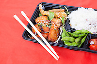 Healthy food served in tray with chopsticks over red background