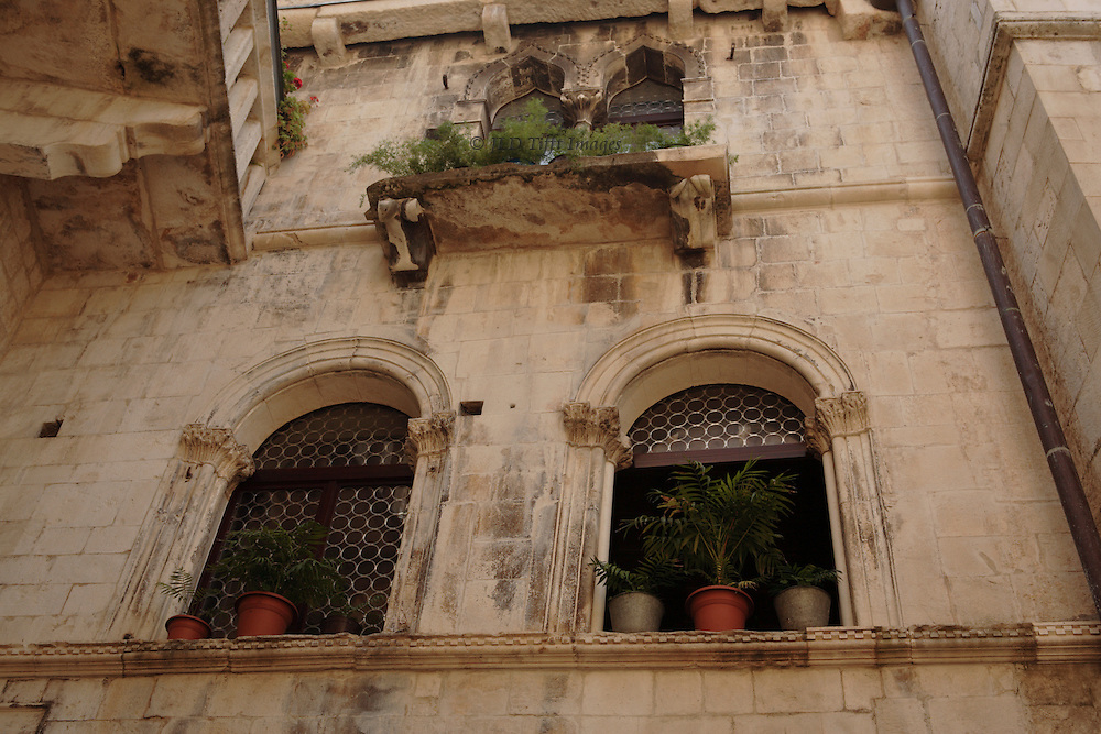 Point of view looking up at a pair of windows and a balcony, lined with potted plants, in a medieval/Renaissance dwelling in Trogir.  The entire old town section is designated a UNESCO World Heritage Site.