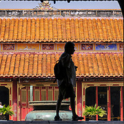 A tourist is silhouetted against To Mieu Temple at the Imperial City in Hue, Vietnam. A self-enclosed and fortified palace, the complex includes the Purple Forbidden City, which was the inner sanctum of the imperial household, as well as temples, courtyards, gardens, and other buildings. Much of the Imperial City was damaged or destroyed during the Vietnam War. It is now designated as a UNESCO World Heritage site.