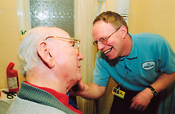 Home helper caring for elderly man in sheltered accommodation Bradford Yorkshire UK
