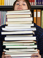 Young man peeking over pile of books
