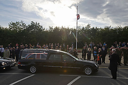 © licensed to London News Pictures. 08/09/2011. Brize Norton, UK..The Body of Sergeant Barry Weston of 42 Commando Royal Marines passes the memorial in Carterton after arriving at RAF Brize Norton for the first time. Sgt Weston was killed on August 30 while leading a patrol near the village of Sukmanda in southern Nahr-e Saraj, Helmand province. Photo credit: Ben Cawthra/LNP