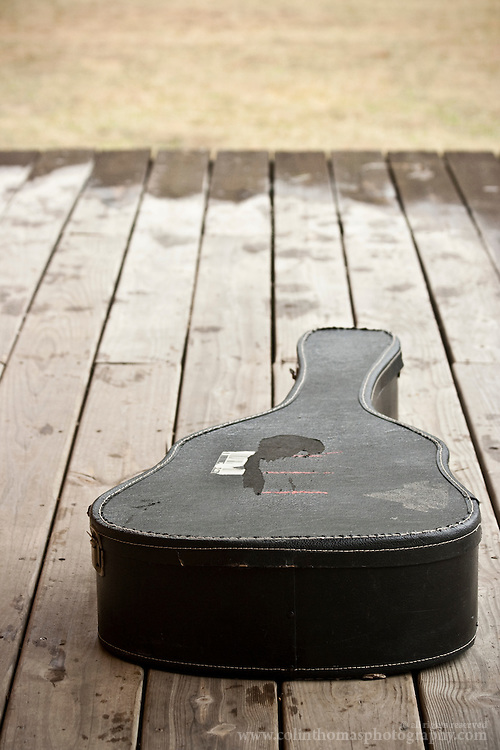Guitar case sitting outside on a wood porch.