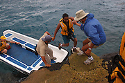 Galapagos Islands - Tuesday, Dec 31 2002: Assisted by two guides, Lorna Brooks disembarks from a rib on to land. (Photo by Peter Horrell / http://www.peterhorrell.com)