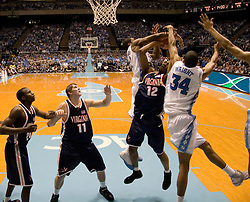UNC's Brandan Wright (34) and Alex Stepheson (32) block Virginia's Jamil Tucker (12) as he attempts a shot.  The #1 ranked Tar Heels beat the Cavaliers 79-69 to improved to 15-1 overall, 2-0 ACC on January 10, 2007 at the Dean Smith Center in Chapel Hill, NC...<br />
