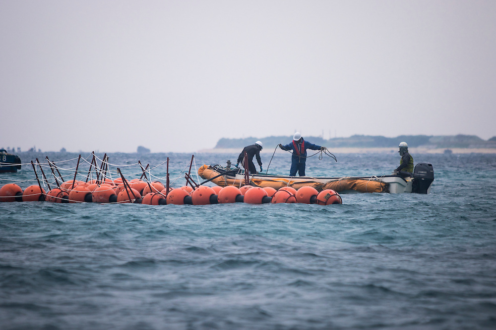 OKINAWA, JAPAN - JANUARY 20 : Workers installs new above-water fencing to keep protest boats out of Henoko construction zone for the new U.S Marine Airbase in Oura Bay, Camp Schwab, Henoko, Nago, Okinawa, Japan on January 20, 2017. The scheduled reclamation area for new the construction totals 160 hectares and will include 2 runways. Construction of the new base will require 21 million cubic meters of soil, enough to fill the Okinawa Prefectural Office 70 times, 17 million tons of which will be hauled in from Kyushu and Shikoku. (Photo by Richard Atrero de Guzman/ANADOLU Agency)