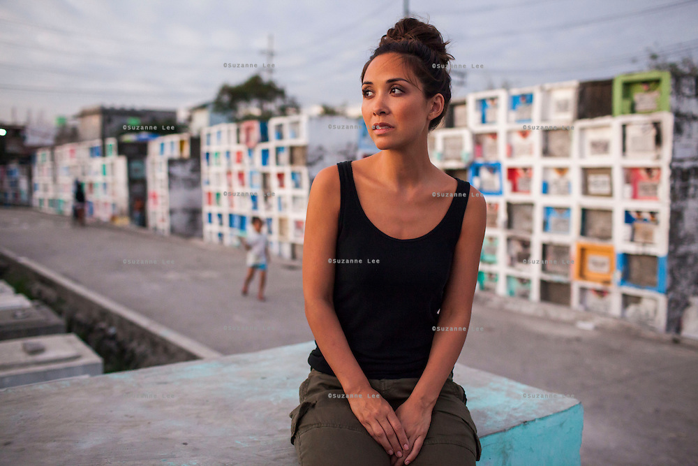 UK celebrity Myleene Klass reflects on the thriving community as she sits on a grave in an inhabited cemetery she is visiting in Paranaque City, Metro Manila, The Philippines on 18 January 2013. Photo by Suzanne Lee for Save the Children UK
