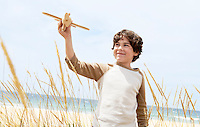 Smiling Pre-teen boy standing arms raised on beach among plants flying toy airplane