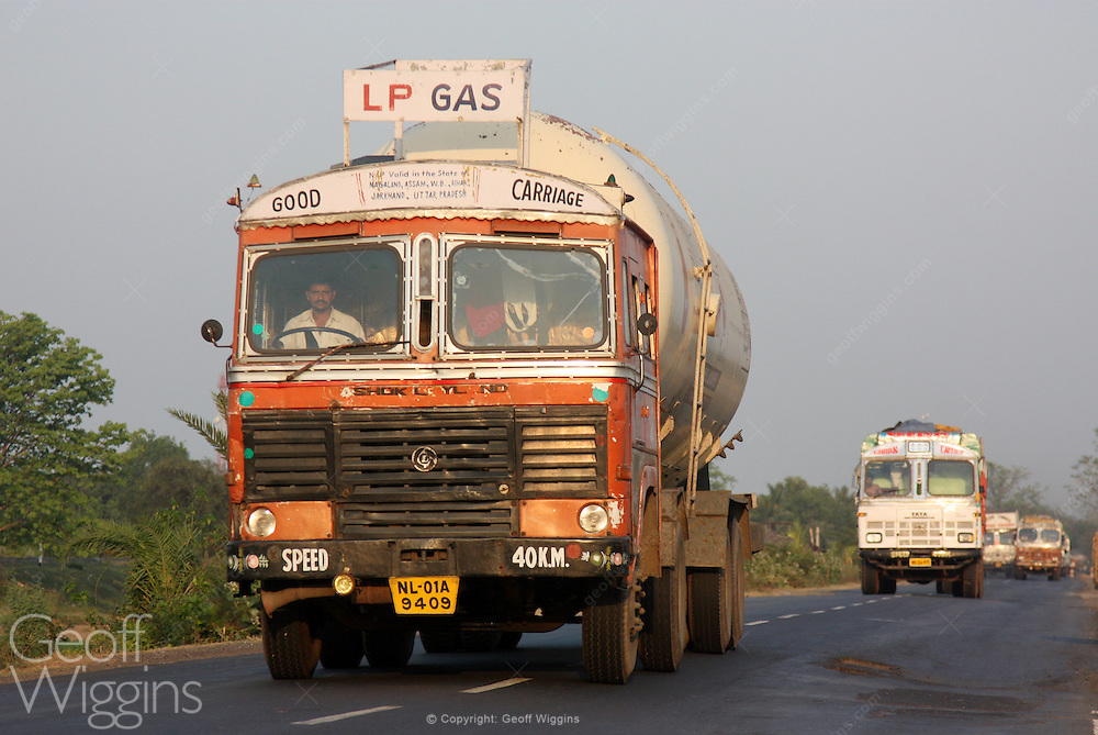 Indian Ashok Leyland LPG gas tanker truck traveling down West Bengal highway at sunset