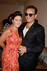 Actress JESSIE WALLACE and TIM ARNOLD at a private view of the late Ian Dury's artwork entitled Ian Dury: More Than Fair – Paintings, drawings and artworks, 1961–1972 held at the Royal College of Art, Kensington Gore, London SW7 on 22nd July 2013.