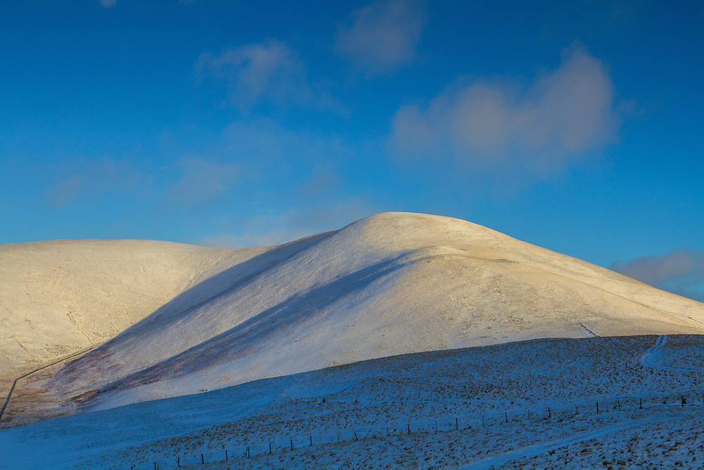 Winter light emerging over the hill 'Trahenna' in Upper Tweeddale in the Scottish Borders
