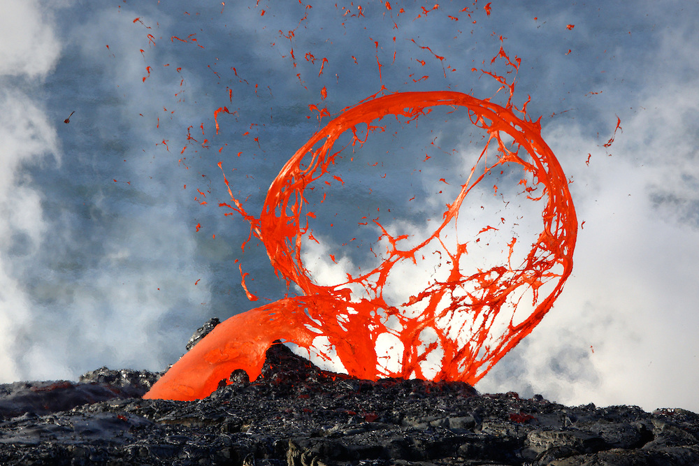 Pressurized steam escapes in a violent lava bubble explosion, creating a circular abstract of volcanic glass extruding through the air.