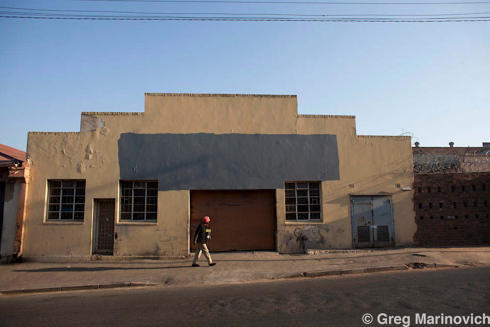 A women cooks and sells food at a corner in an industrial area of Webber, Booysens, Johannesburg.  18 Aug 2010. Photo Greg Marinovich