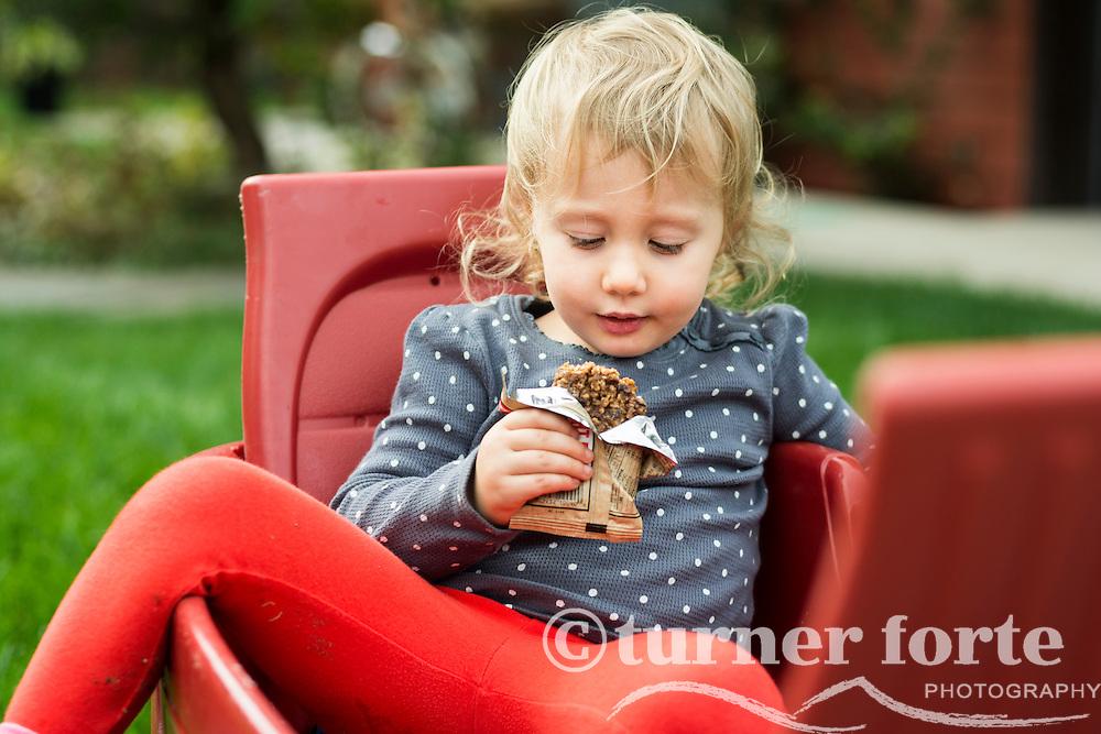 Toddler girl takes snack bar break in red wagon, Portland, Oregon.