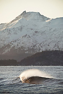 An A-Frame wave peaks and breaks in Kachemak Bay, Alaska on a cold winter morning. The Kenai Mountains stand tall in the background.