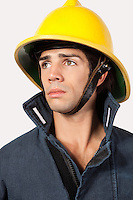 Thoughtful fireman looking away against gray background
