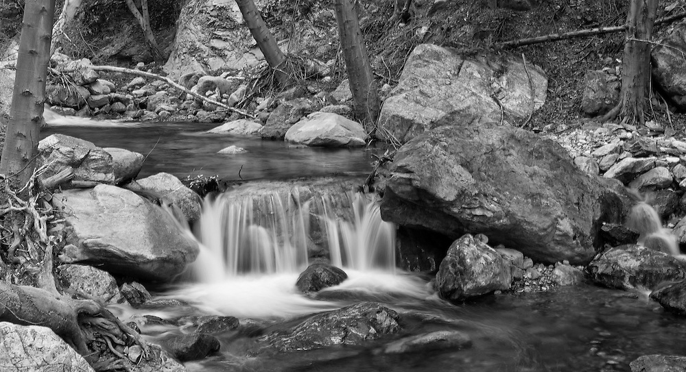 Image of creek in black and white. Image does have a bit of blur to give you the feel of movement.  Can take off with photoshop if needed.  Just email us at info@sullivanjphotography.com
