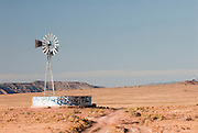 An old windmill in northwest New Mexico with a water collection tank.