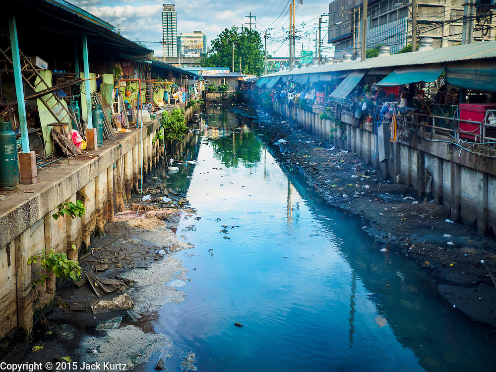 "12 JUNE 2015 - BANGKOK, THAILAND: A waste water canal running through Khlong Toey Market in Bangkok. Khlong Toey Market in Bangkok. Khlong Toey (also called Khlong Toei) Market is one of the largest ""wet markets"" in Thailand. The market is located in the midst of one of Bangkok's largest slum areas and close to the city's original deep water port. Thousands of people live in the neighboring slum area. Thousands more shop in the sprawling market for fresh fruits and vegetables as well meat, fish and poultry.          PHOTO BY JACK KURTZ"