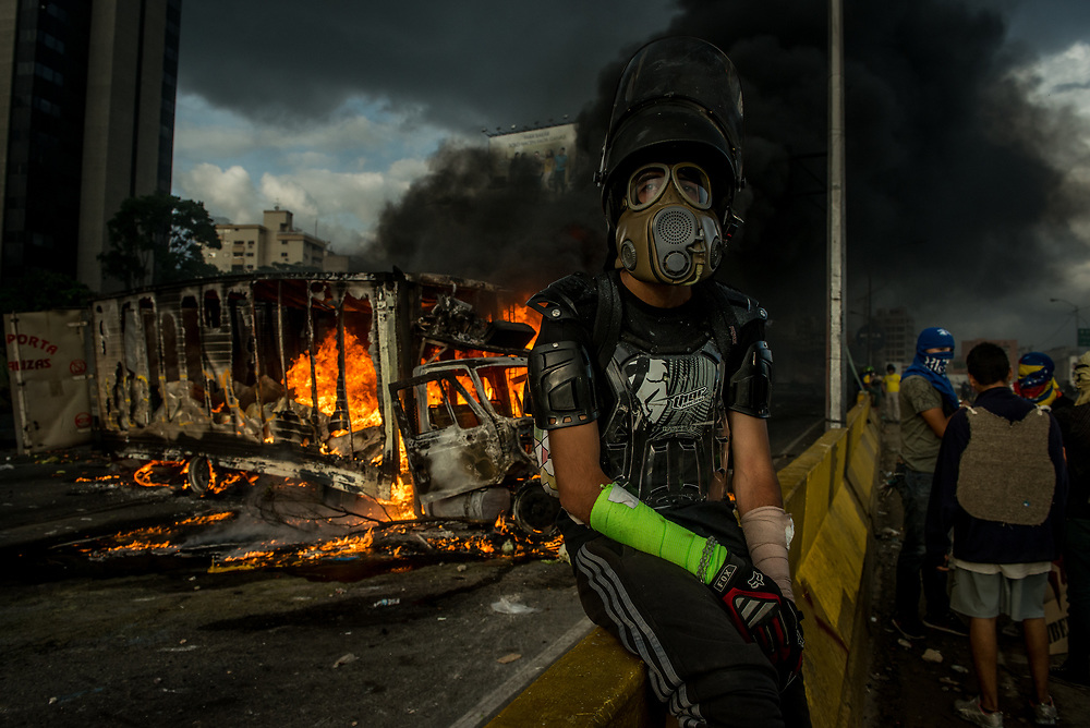 "CARACAS, VENEZUELA - MAY 27, 2017:  An anti-government protester of ""The Resistance"" rests during a lull in fighting as an industrial sized truck that protesters highjacked and used as a roadblock after taking over the main highway that runs through Caracas, burns in the background.  The streets of Caracas and other cities across Venezuela have been filled with tens of thousands of demonstrators for nearly 100 days of massive protests, held since April 1st. Protesters are enraged at the government for becoming an increasingly repressive, authoritarian regime that has delayed elections, used armed government loyalist to threaten dissidents, called for the Constitution to be re-written to favor them, jailed and tortured protesters and members of the political opposition, and whose corruption and failed economic policy has caused the current economic crisis that has led to widespread food and medicine shortages across the country.  Independent local media report nearly 100 people have been killed during protests and protest-related riots and looting.  The government currently only officially reports 75 deaths.  Over 2,000 people have been injured, and over 3,000 protesters have been detained by authorities.  PHOTO: Meridith Kohut"