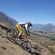 Kurt Summerfield in action during the New Zealand South Island Downhill Cup Mountain Bike series held on The Remarkables face with a stunning backdrop of the Wakatipu Basin. 150 riders took part in the two day event. Queenstown, Otago, New Zealand. 9th January 2012. Photo Tim Clayton