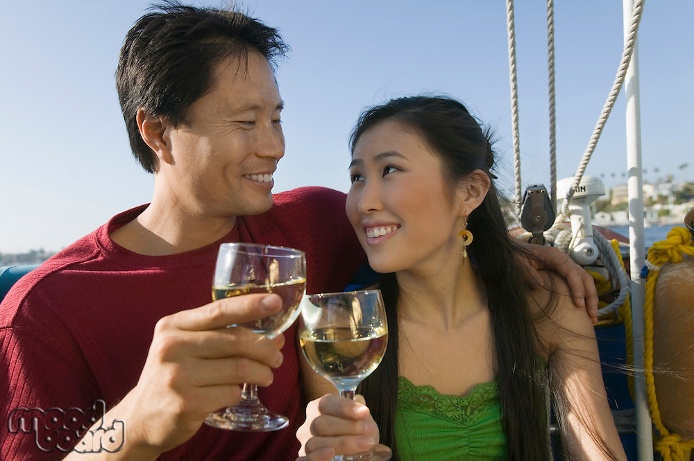 Couple toasting with white wine on boat