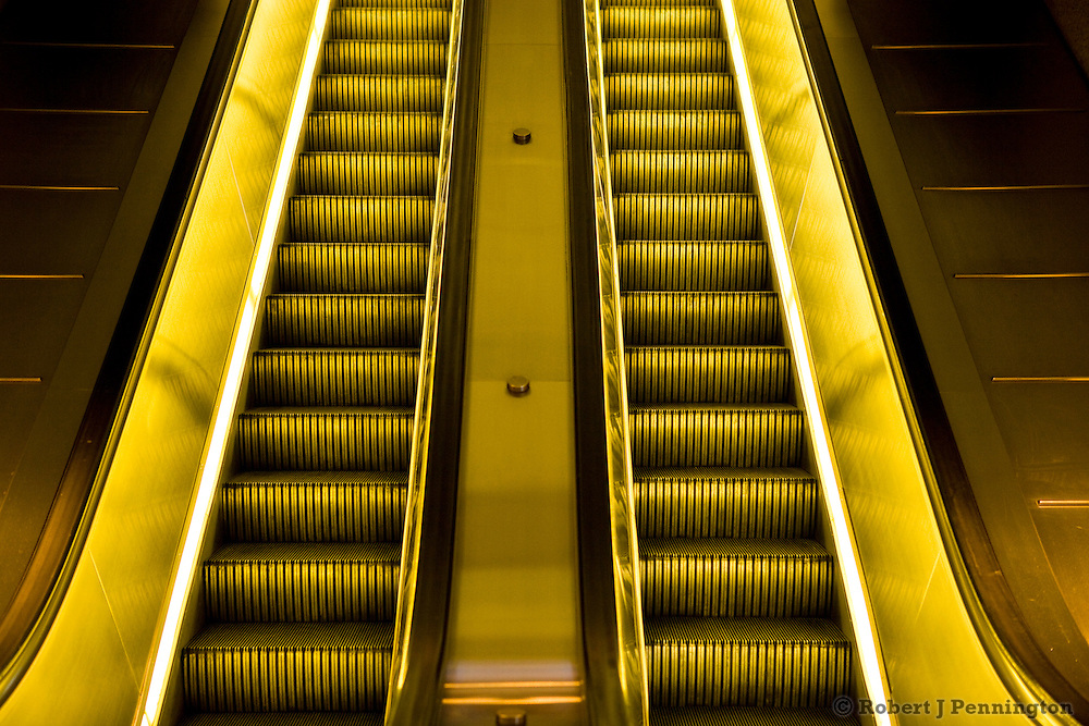 Artificial lights glow gold and yellow from two stationary escalators with no people.