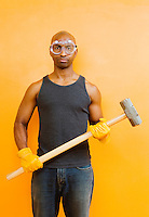 Portrait of a mid 30's African American man wearing gloves, protective goggles, and holding a sledgehammer...model release: 20060425_MR_A