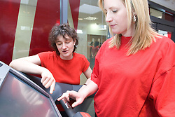 Fitness instructor showing woman how to use the settings on a treadmill machine at her sports leisure centre,