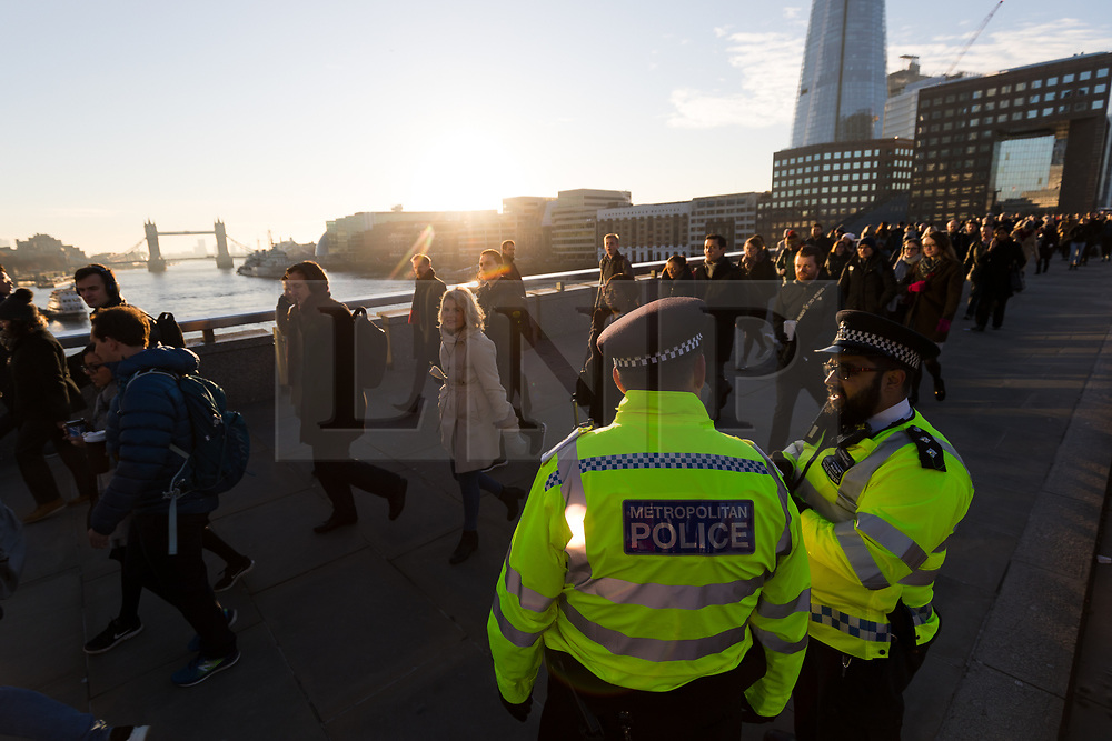 © Licensed to London News Pictures. 02/12/2019. London, UK. Police officers on London Bridge as commuters walk to work on London Bridge. Two victims were died following a terrorist attack near London Bridge on 29th November when police shot dead the attacker. Photo credit: Vickie Flores/LNP