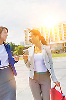 Businesswomen holding a cup of coffee while talking on the road