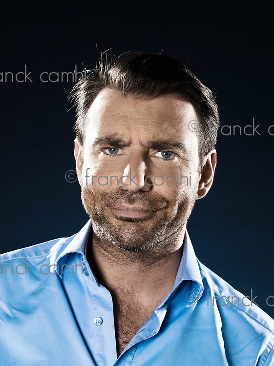 caucasian man unshaven suspicious doubt portrait isolated studio on black background