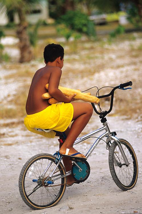 French Polynesia Rangiroa Atoll Tuamotu Archipelago boy fetching French bread on his bicycle